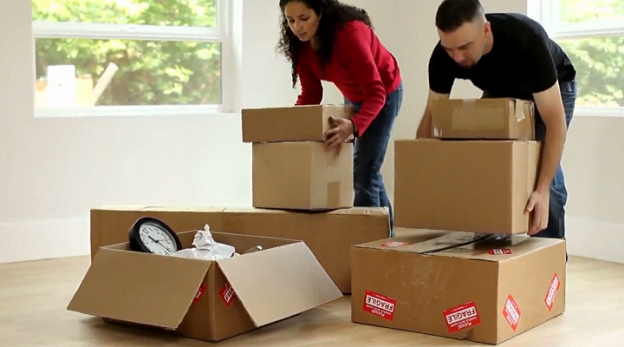 a couple moving and packing boxes